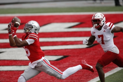 Ohio State receiver Garrett Wilson, left, catches a touchdown pass past Nebraska defensive back Dicaprio Bootle during the first half of an NCAA college football game Saturday, Oct. 24, 2020, in Columbus, Ohio.