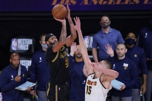 Los Angeles Lakers' Anthony Davis (3) shoots a 3-point basket over Denver Nuggets' Nikola Jokic (15) at the end of an NBA conference final playoff basketball game Sunday, Sept. 20, 2020, in Lake Buena Vista, Fla. The Lakers won 105-103.