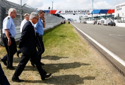 Roger Lewentz, interior minister of the federal state of Rhineland-Palatinate is escorted by police as he walks over Germany's Formula One racing track Nuerburgring, Germany June 3, 2017.